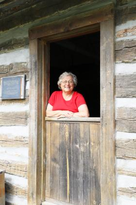 Volunteer extraordinaire — Debby Krohe of Virginia is pictured at the Dutch door of a cabin at Rexroat Prairie, one of the many projects to which she devotes her time. (Photo by Brian DeLoche.)