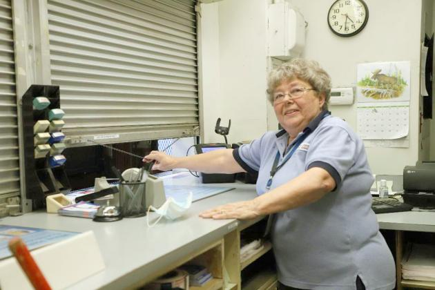 It's Quittin' Time! — With the clock on the wall reading 4:31 p.m, Rose Black closes the service window at the Beardstown Post Office for the last time on Friday, July 3, ending her remarkable 47-year career with the U.S. Postal Service.  (Photo by Brian DeLoche)