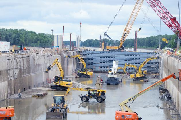 Tight quarters— Heavy equipment operators have to keep their heads on swivels to operate safely and avoid other heavy machines operating in the tight space of the lock chamber at the LaGrange Lock & Dam. (Photo by Brian DeLoche.)