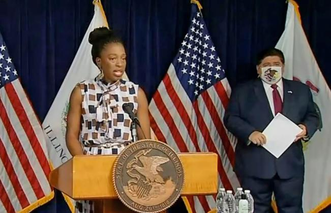 llinois Department of Public Health Director Dr. Ngozi Ezike speaks at a COVID-19 news conference in Chicago Wednesday as Gov. JB Pritzker looks on. (Credit: Blueroomstream.com)