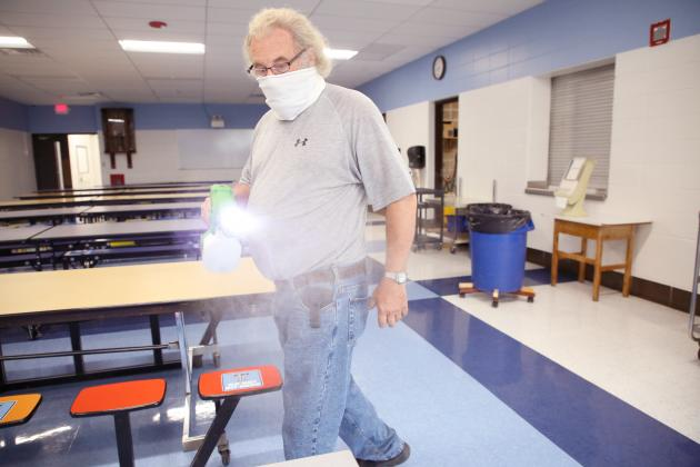 Spraying it safe — Roger Graves uses an electro static sprayer to disinfect Triopia's cafeteria area Tuesday morning. (Photo by Brian DeLoche)