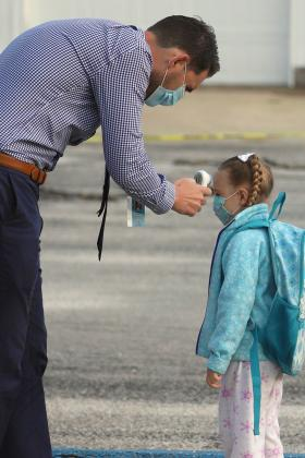 District 27 Superintendent Adam Dean checks Griffin Wardell's temperature prior to her entering the school building. (Photo by Brian DeLoche.)