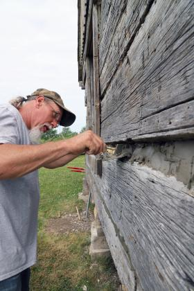 "Artist at work — With a pallet of cement and mortar, Ruppert Parrish artfully fills in the gaps between the logs of a cabin wall at The Rexroat Prairie in Virginia. The material between the logs is called chinking, and works to keep wind and moisture out of the cabin and helps prevent decay. At right is the ""Dog Trot"" cabin, so named because the center space allowed dogs to trot in and out. (Photo by Brian DeLoche.)"