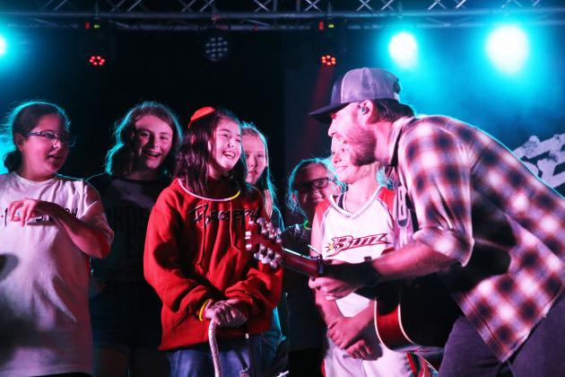 "This song's for you ­­— Brock Jones, lead singer for the band ""Broseph"" turns his attention to Alayna Capps during a concert Saturday night highlighting a weekend of fundraising activities to help off set medical and travel expenses connected to her fight with a brain tumor. (Photo by Brian DeLoche.)"