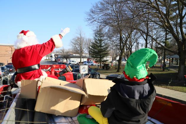 Santa, in the company of one of his most trusted elves, waves to children from the back of a firetruck as he led a caravan of emergency vehicles with lights flashing and sirens wailing through the village streets  (Photos by Brian DeLoche.)