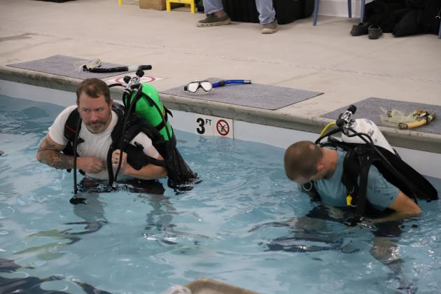 Brian Becker and Alex Davidsmeier strap on their air bottles and buoyancy compensating devices for the first time. (Photos by Brian DeLoche.)